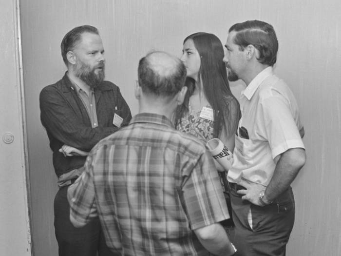 Image: Philip K. Dick, Nancy Dick, and Robert Silverberg conversing in lobby, Baycon, 1968. -- From Jay Kay Klein Photographs and Papers on Science Fiction Fandom