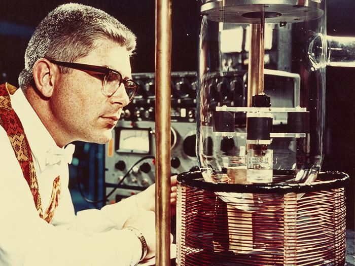 Robert Forward looking intently at a piece of scientific equipment (MS175, Box 1, Folder 2)