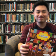"""UCR alumnus and former library student employee Matthew Diep holding a copy of his first children's book, """"There's a Book on That"""""""