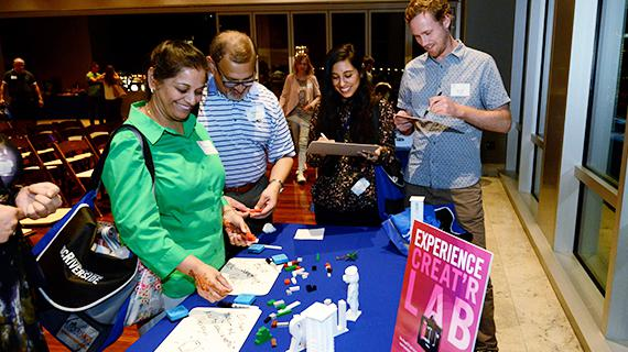 3D printed models of UCR campus icons being enjoyed by alumni at a San Diego reception