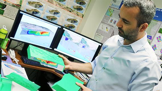 """Christodoulos Kyriakopoulos holding his model of the 2010 El Mayor-Cucapah (Baja California, Mexico) earthquake. Note: In the back of the photo you can see a video screen playing the actual numerical simulation of the same earthquake."""""""