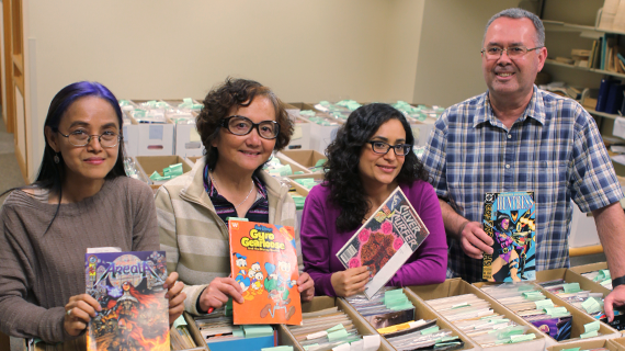 Sompratana, Min, Erika and Jim pictured with the comic books their team sorted