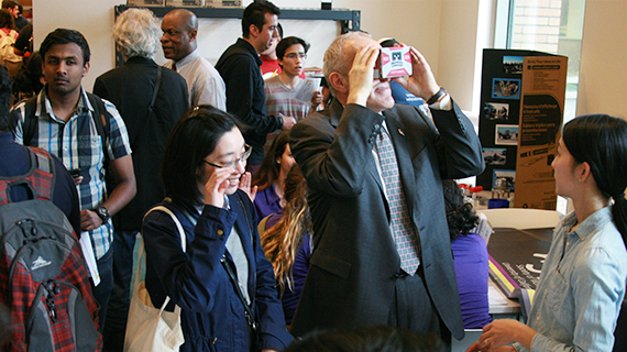 Chancellor Kim Wilcox tries on a pair of virtual reality goggles at UCR Library's Creat'R Lab launch
