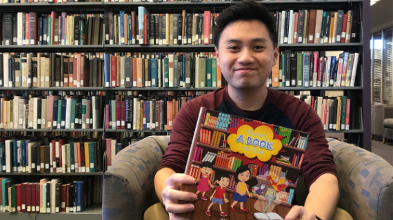 "UCR alumnus and former library student employee Matthew Diep holding a copy of his first children's book, ""There's a Book on That"""