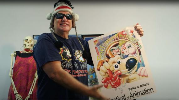 """Craig """"Spike"""" Decker holding up a poster from Spike & Mike's Animation Festival"""