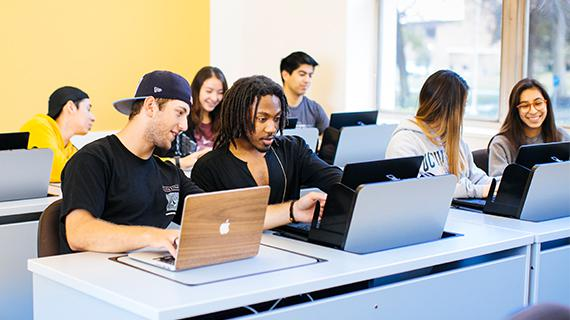 Students researching content on laptop computers
